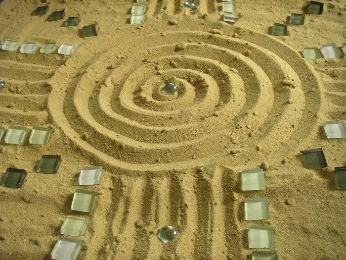 Das Sandspiel dient als gestalterisches Element in der Psychotherapie